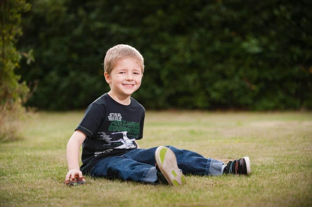 Child location portrait sitting in the front garden